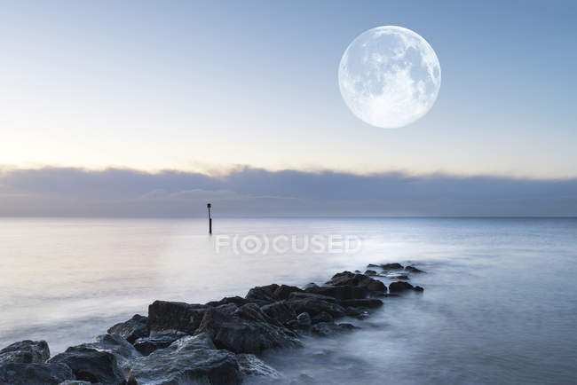 Landscape over rocks in sea with giant moon — Stock Photo
