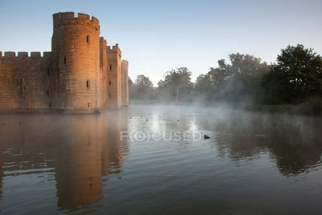 Beautiful medieval castle and moat at sunrise — Stock Photo