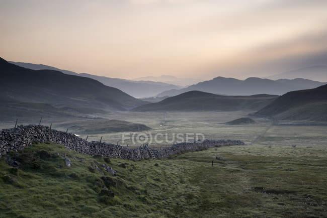 Campos del campo hacia la brumosa montaña de Snowdonia - foto de stock