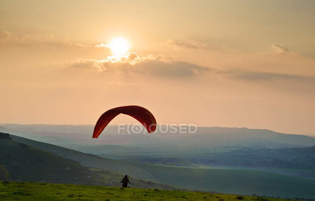 Paraglider takes off into setting sun — Stock Photo