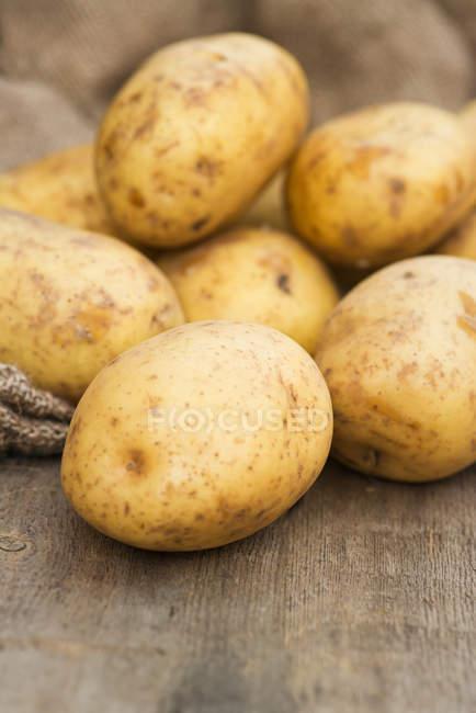 Haufen von Kartoffeln auf Holztisch — Stockfoto