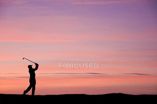 Mann spielt Golf bei buntem Sonnenuntergang — Stockfoto
