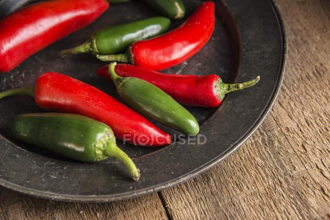 Червоний і зелений перець на тарілку — стокове фото