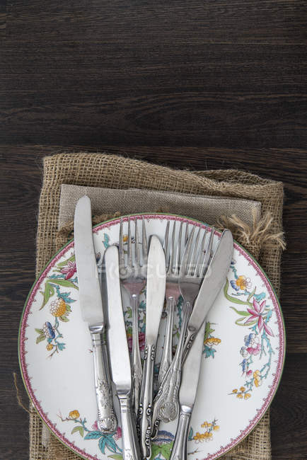 Vintage cutlery and crockery on cloths — Stock Photo