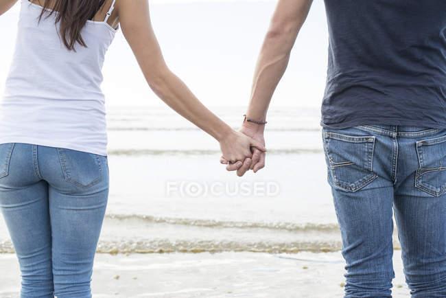 Пара ходить держась за руки через пляж — стоковое фото