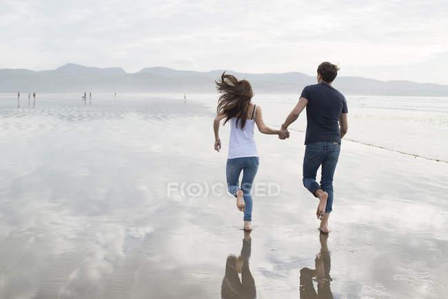 Pareja corriendo mientras toma de la mano en la playa - foto de stock