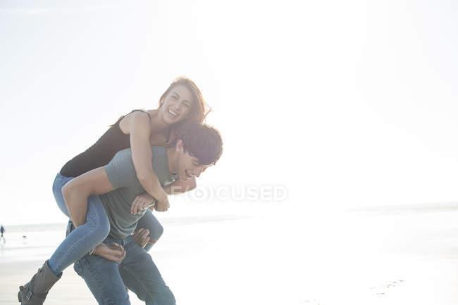 Людина, даючи piggyback їздити подруга — стокове фото