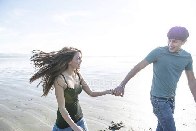 Пара ходьби, тримаючись за руки по пляжу — стокове фото