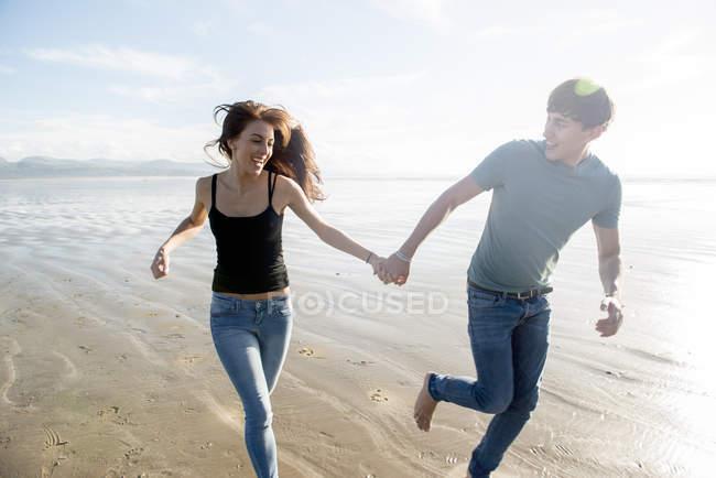 Coppia correre mentre si tiene per mano sulla spiaggia — Foto stock