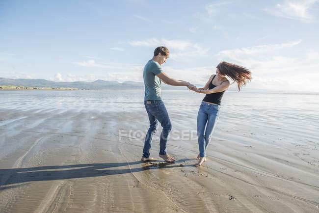 Пара тримається за руки на пляжі. — стокове фото