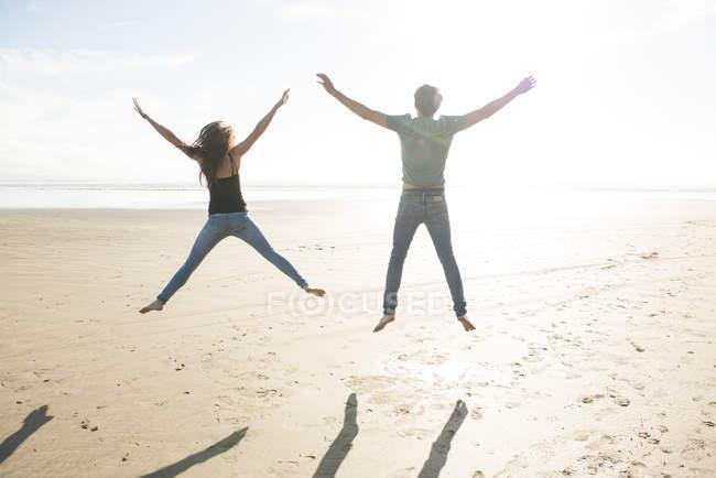 Couple jumping in sunshine on beach — Stock Photo