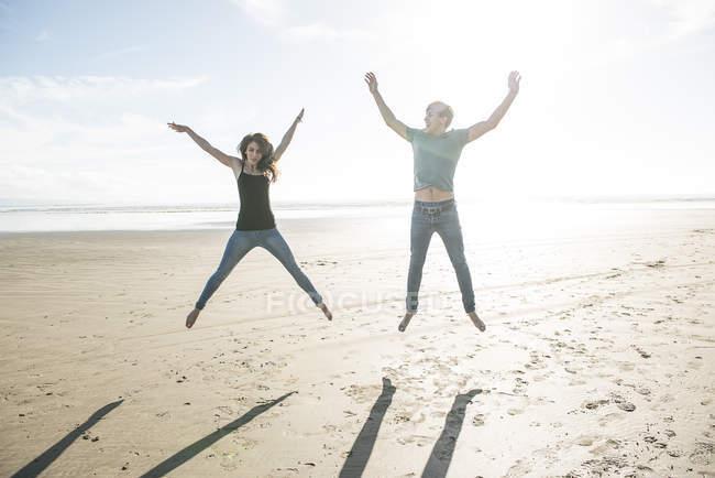 Пара, прыгающая в лучах солнца на пляже — стоковое фото