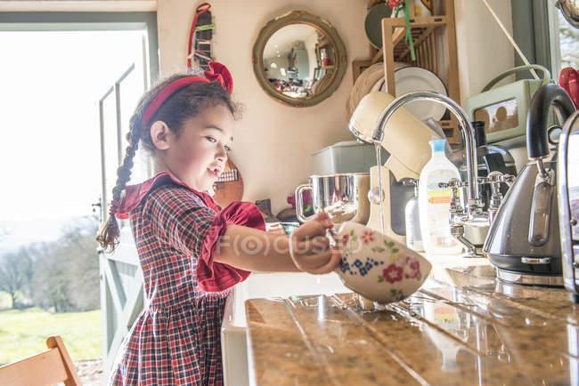 Chica lavando platos en fregadero de cocina - foto de stock