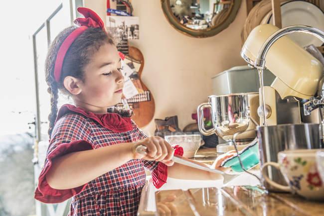 Девушка моет посуду в раковине — стоковое фото