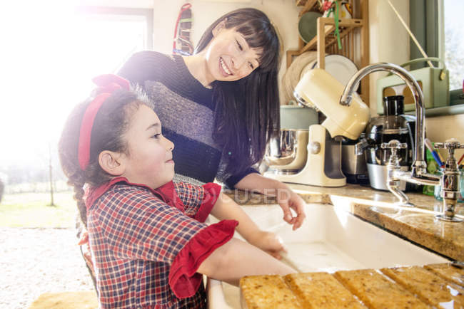 Girl with mother washing dishes — Stock Photo