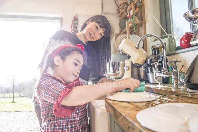 Chica con la madre lavando platos - foto de stock