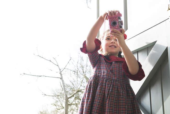 Menina tirando foto com câmera de brinquedo — Fotografia de Stock