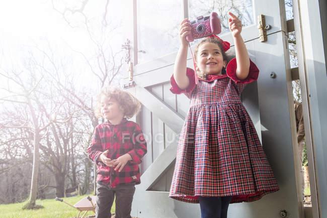 Menina com irmão tirando fotos com câmera de brinquedo — Fotografia de Stock