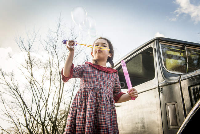 Girl blowing bubbles in front of car — Stock Photo