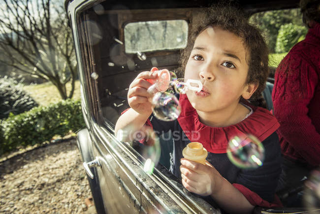Girl blowing bubbles out of window — Stock Photo