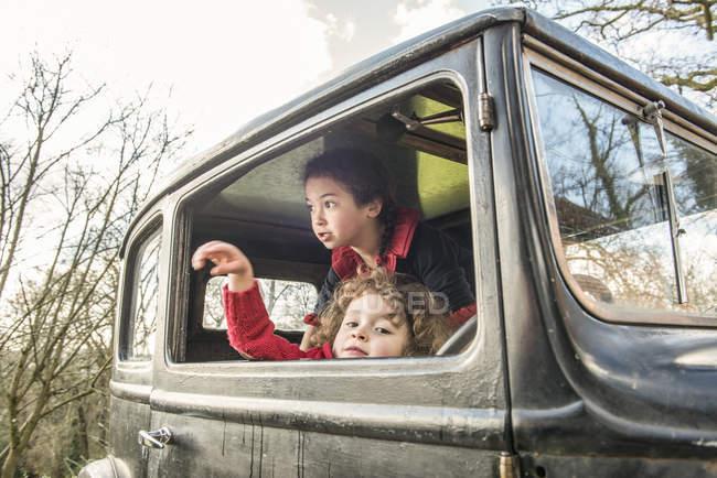 Niños jugando en coches de época - foto de stock