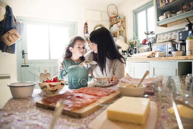 Девушка, будучи утешает мать обеденным столом — стоковое фото