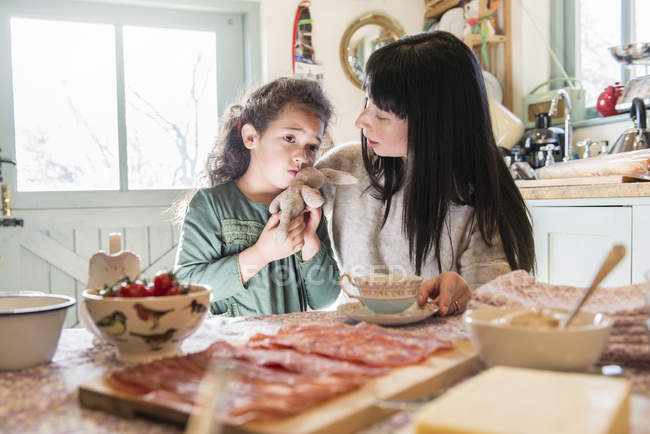 Girl being comforted by mother at dinner table — Stock Photo