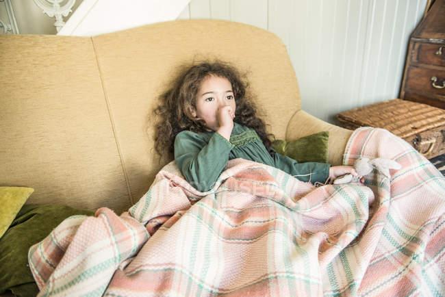 Девушка держит игрушечного кролика сидя на диване — стоковое фото