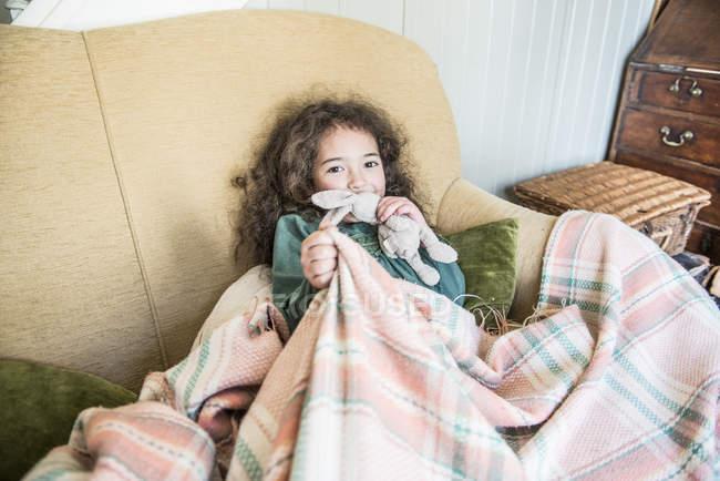 Девочка держит игрушка кролик, сидя на диване — стоковое фото