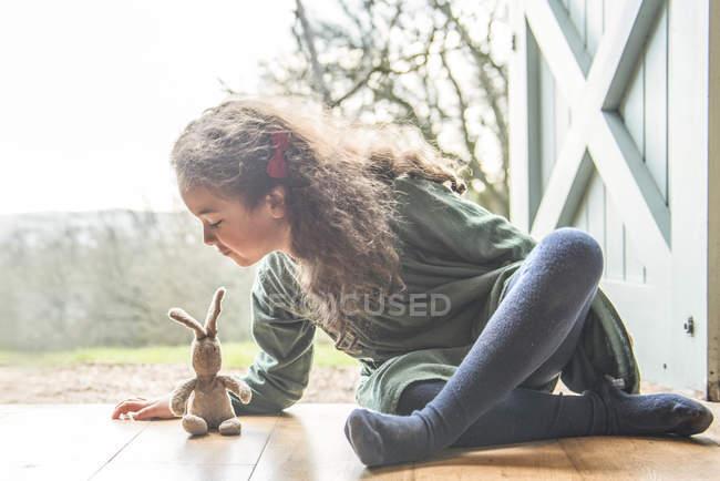 Девочка сидит на задней двери, играя с игрушка кролик — стоковое фото