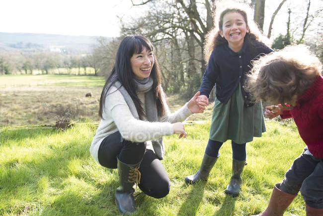 Madre e hijos disfrutando de estar en el jardín - foto de stock