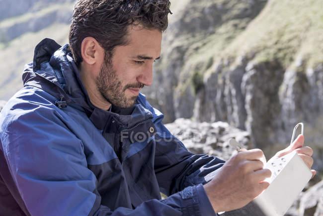Альпинист сидит и ест пищу — стоковое фото
