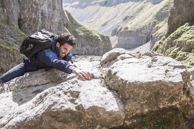 Mountaineer climbing over rocks in rugged terrain — Stock Photo