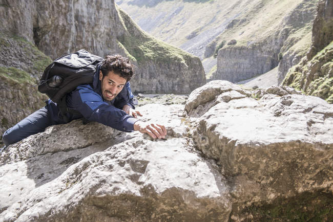 Mountaineer climbing over rocks in rugged terrain — Stock Photo