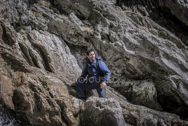 Mountaineer sitting over rocks in rugged terrain — Stock Photo