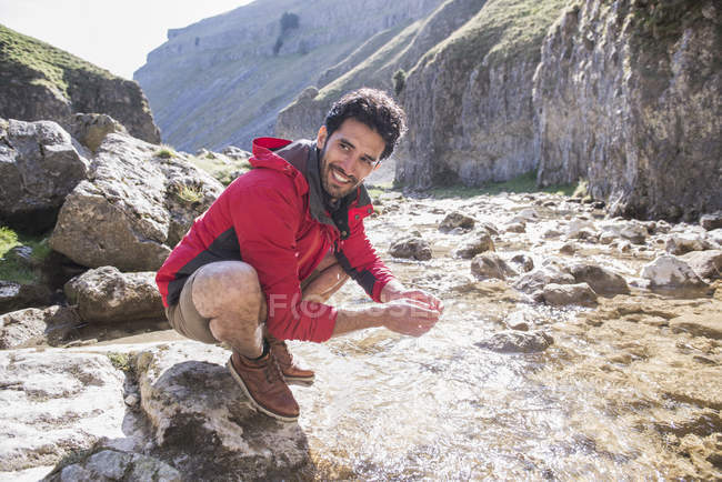 Bergsteiger hält an, um sich in Gebirgsbach zu waschen — Stockfoto