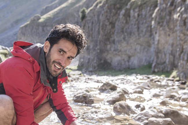 Alpiniste s'arrêtant pour se laver dans le ruisseau de montagne — Photo de stock