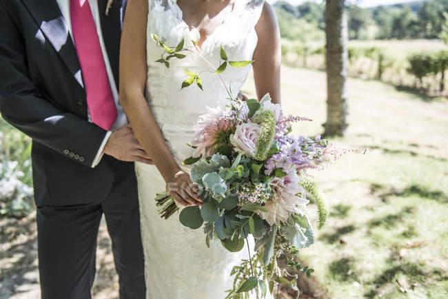 Mariée et le marié avec bouquet de fleurs — Photo de stock