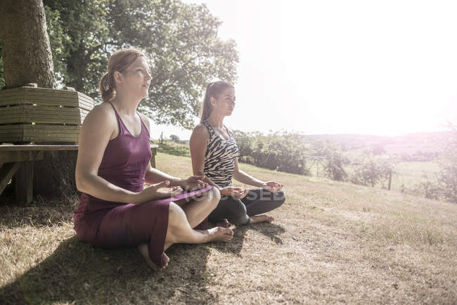 Friends sit at meadow and practice yoga — Stock Photo