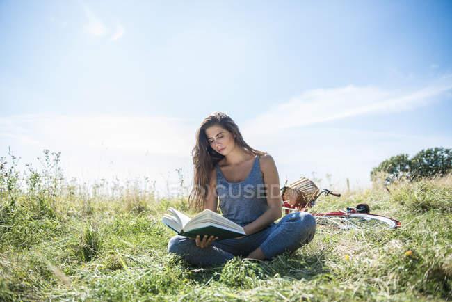 Femme lisant le livre tout en restant assis dans Prairie — Photo de stock