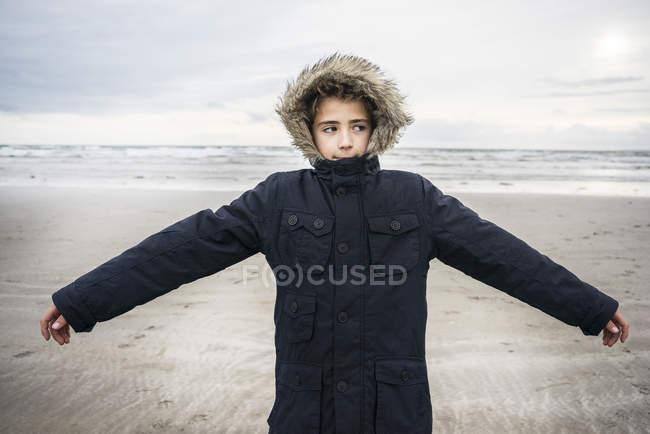 Junge stand am Strand mit ausgestreckten Armen — Stockfoto