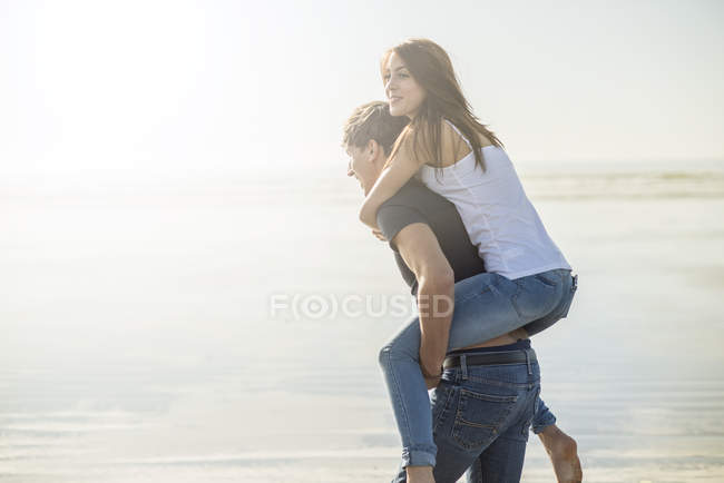 Man giving piggyback ride to female friend — Stock Photo