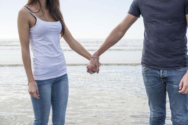 Couple standing on beach and holding hands — Stock Photo