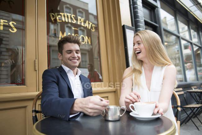 Amigos sentado fuera del café - foto de stock