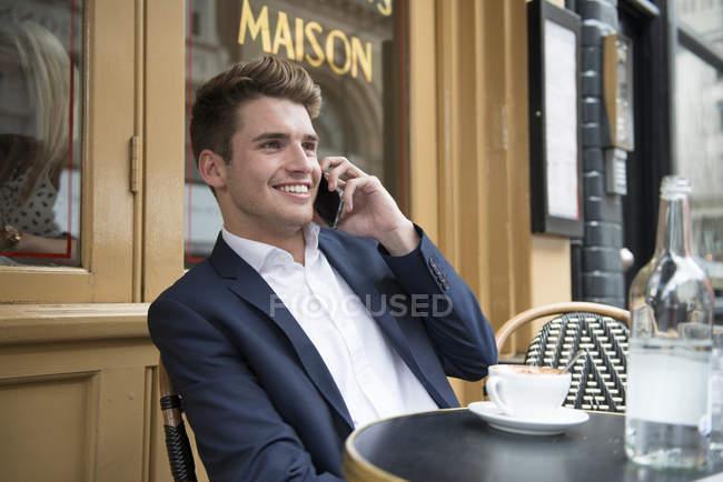 Hombre sentado fuera de café en el teléfono - foto de stock