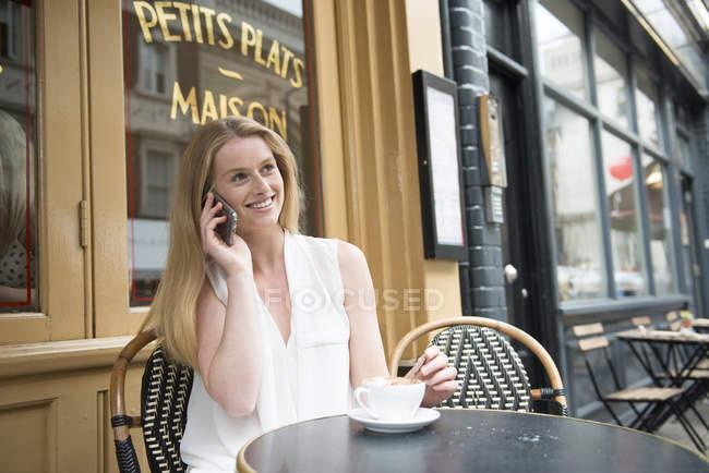 Женщина, сидящая снаружи кафе и разговаривающая по телефону — стоковое фото