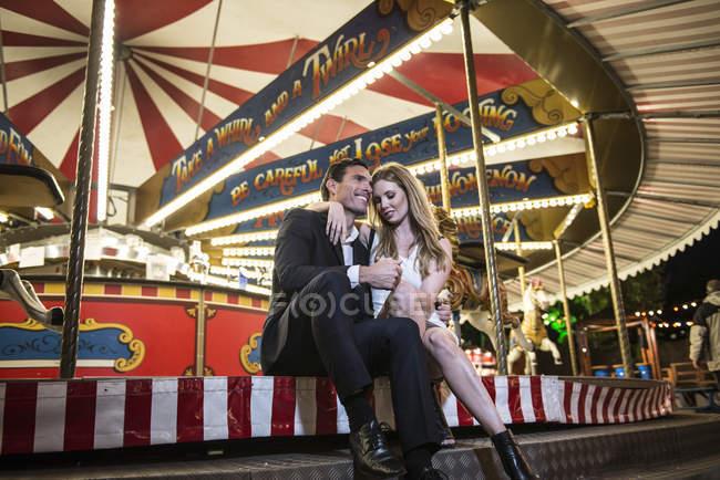 Paar kuschelt mit Karussell — Stockfoto