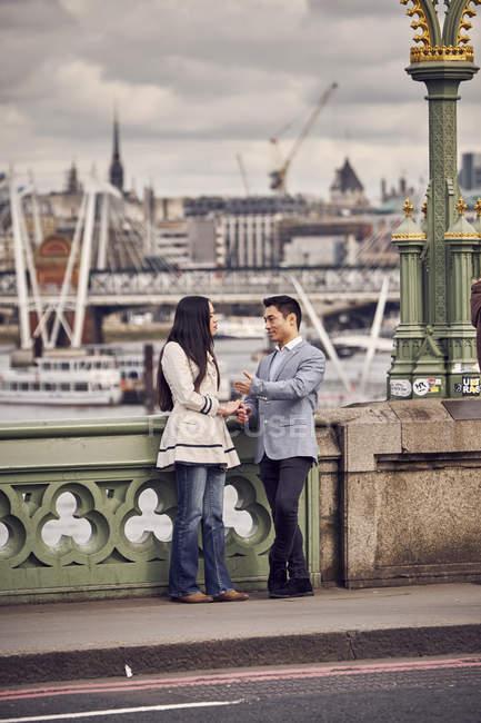 Casal falando enquanto está em pé na ponte — Fotografia de Stock