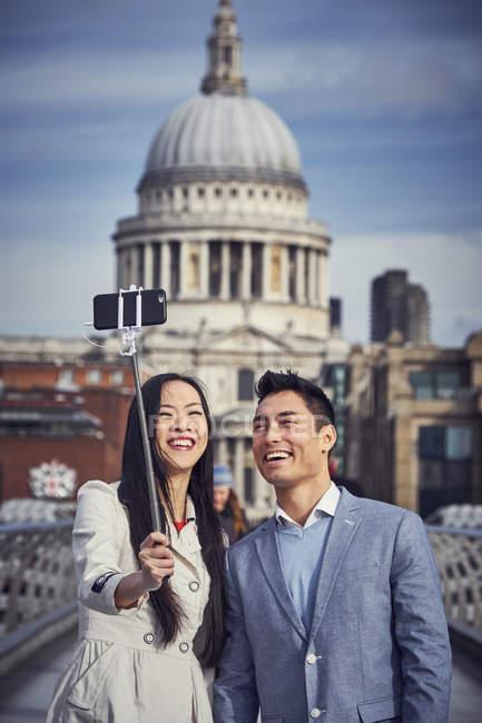 Couple prendre selfie tandis que debout à Millennium Bridge — Photo de stock