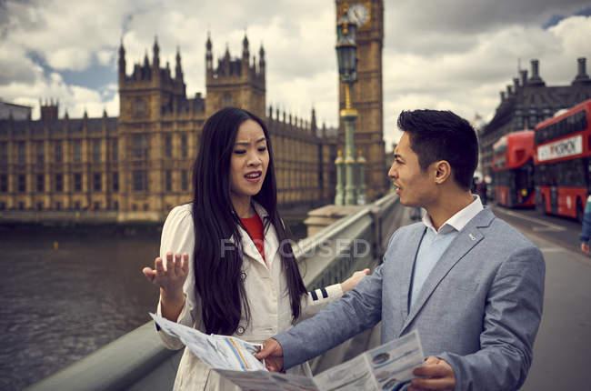 Пара, утверждая, глядя на карту путешествия — стоковое фото